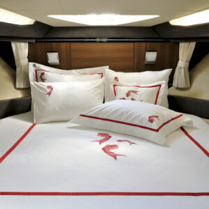 Fish patterned white & red colored sheet set in a modern furnitured sailboat cabin