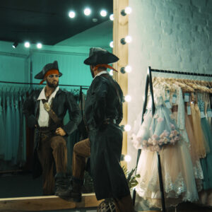 Back view of man wearing costume of pirate and standing in front of mirror in dressing room practicing scene from performance