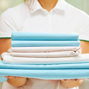 Closeup of woman's hand holding a stack of clean folded bed sheets of blue and white colors. Blurred background.